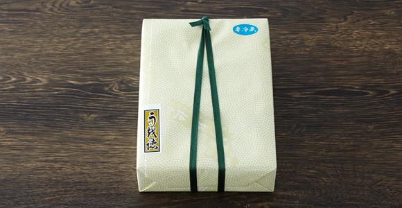 鮫小紋柄の包みとオリジナルの千社札。老舗料亭らしい贅沢な贈り物